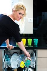 Blonde Frau räumt Geschirr ein