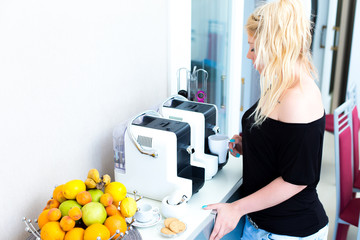 Blonde Frau an der Kaffeemaschine