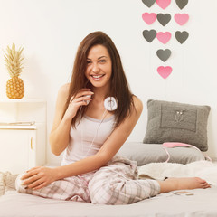 Young woman with headphones relaxing in bed in the morning