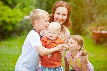 Familie mit Baby und Kindern im Garten