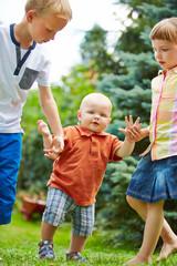 Geschwister helfen Baby beim Laufen lernen