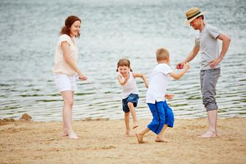 Familie mit Kindern beim Seilspringen am Strand