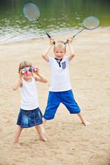 Zwei Kinder am Strand spielen mit Federball Ausrüstung