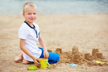 Kind baut Sandburg am Strand