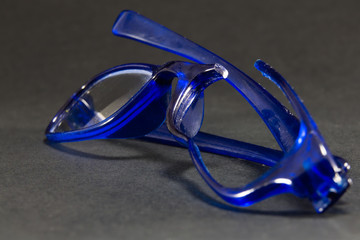 blue broken glasses on black background