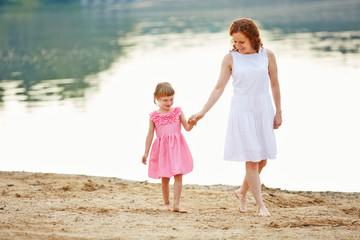 Mutter und Tochter machen Spaziergang am Strand