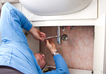 a plumber repairing a broken sink in bathroom