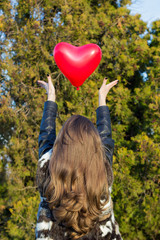 Girl throwing a balloon in the shape of heart