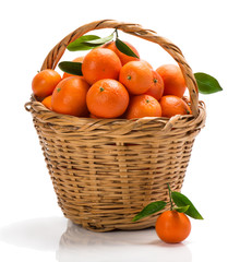 ripe tangerines with green leaves in basket