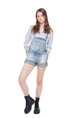 Young fashion girl in jeans overalls posing isolated