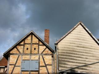 Giebel alter Bauernhäuser vor Regenwolken in Salzböden
