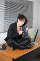 Femme sur son bureau en tailleur dépitée sur son bureau