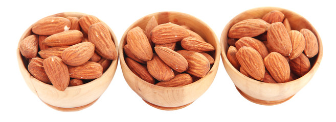 Almond in wooden bowls, isolated on white