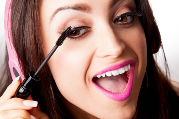 Woman Putting on mascara while listening to Headphones