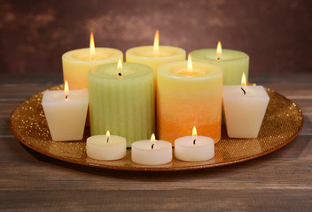 Beautiful candles on table on brown background