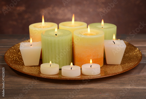 canvas print picture Beautiful candles on table on brown background
