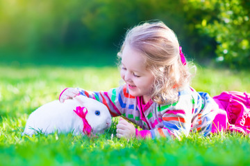 Adorable little girl and real rabbit