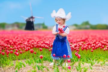 Sweet dutch girl in tulip field in Holland