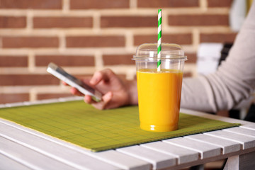 Orange juice in fast food closed cup with tube and mobile phone