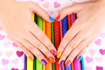 Multicolor female manicure with markers and pencils