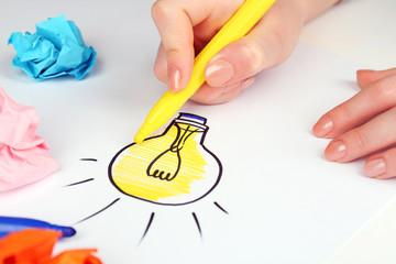 Female hand drawing symbol of idea as light bulb