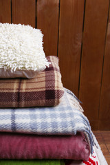 Pile of warm plaids and pillow on rustic wooden background