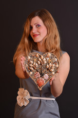 Beautiful young blonde woman with heart gift made by seashells