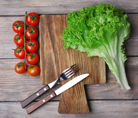 Cutting board with cherry tomatoes and lettuce