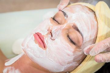 Cosmetology spa facial. Beautiful brunette in a spa salon