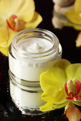 Face cream with orchid flowers on dark background