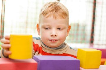 Little boy play construction set..