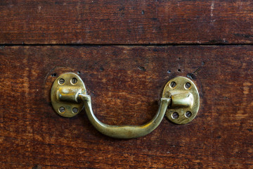 brass handle of an old rustic wooden chest.