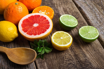 Halves of citrus fruits on wooden background. Orange, grapefruit