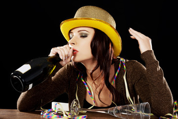 Young drunk woman  with empty champagne bottle