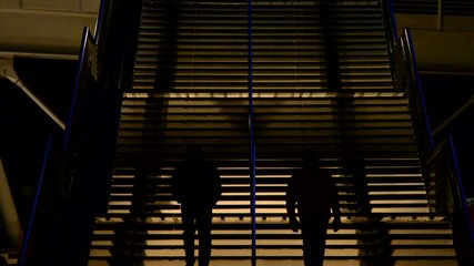 Silhouetted people climb a stairwell in the city