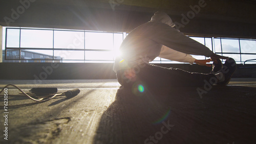 Hooded athlete stretching before or after a workout - 76230560
