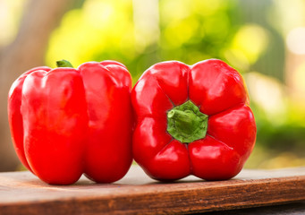 Fresh red pepper on wooden table on nature background