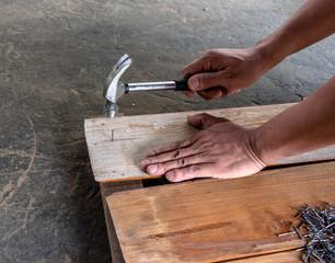 carpenter nailing wood board by hammer
