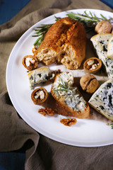 Blue cheese with sprigs of rosemary, bread and nuts