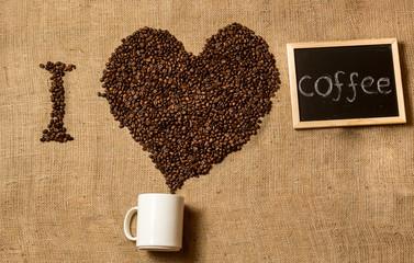 """I love coffee"" spelled by coffee beans, coffee mug and chalk bo"