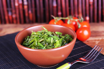 Seaweed salad in bowl with cherry tomatoes
