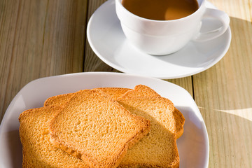 Breakfast time: cup of milky coffee and rusks