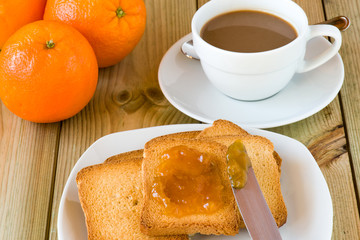 Breakfast time: cup of milky coffee, rusks and orange jam on woo