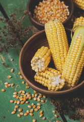 Corn on the plate on a green wooden boards