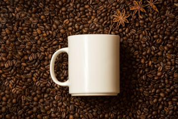 white mug against coffee beans with anise stars lying like steam