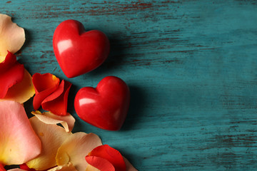 Rose petals and decorative hearts on wooden background