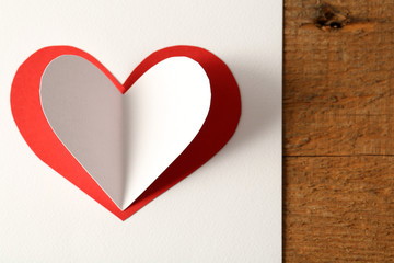 Beautiful paper heart on white paper background, close-up
