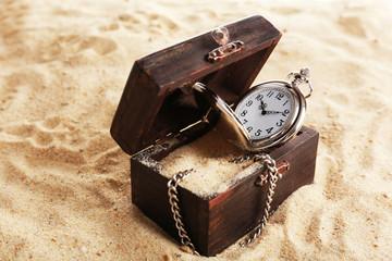 Silver pocket clock on sand background
