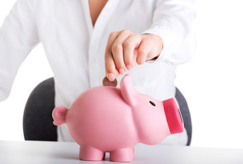 Happy businesswoman holding piggy bank