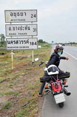 Woman riding chopper motorcycle on the way with Distance signs